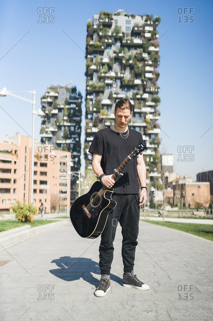 man holding a guitar is standing in front of two green skyscrapers