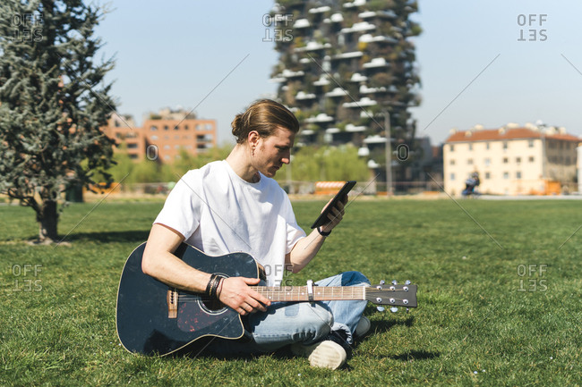 man looking at tablet device holding the guitar in a urban garden