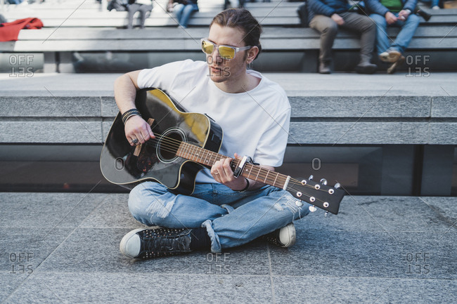 musician is performing outdoor, sitting on the floor with people behind