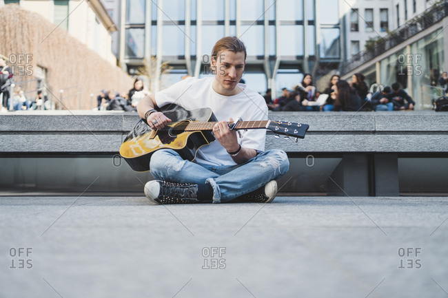 white musician sitting on the floor in a urban square with stone floor