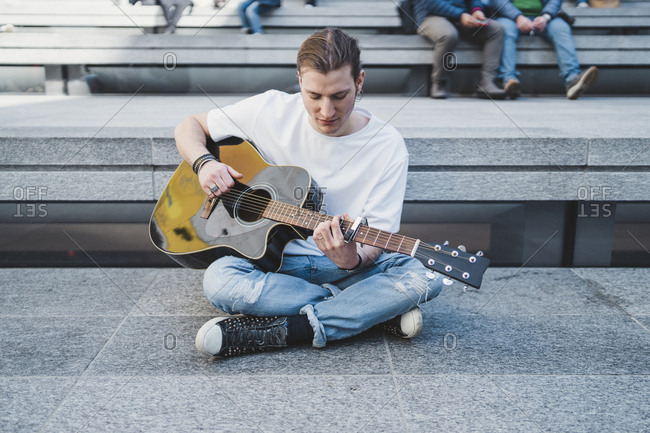 musician looking at the guitar sitting on the floor with people behind