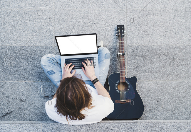 young man long hair writing on laptop sitting next acoustic guitar