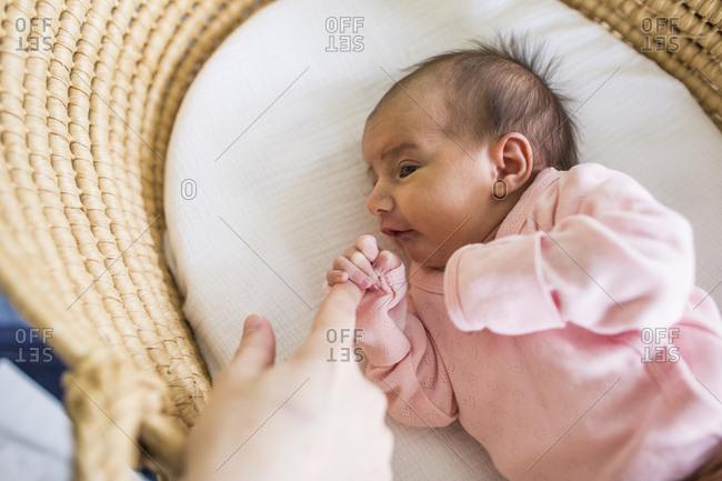 Newborn girl holding mothers finger