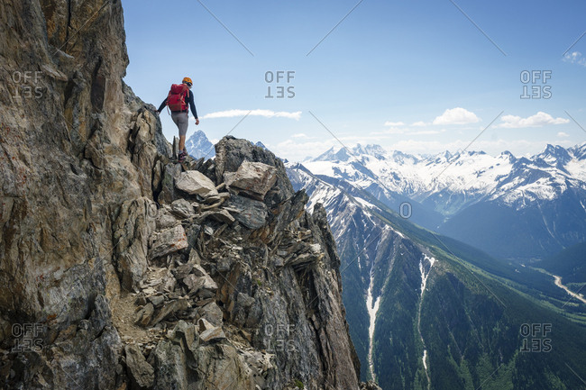 Male mountaineer walking on the edge of cliff, British Columbia Canada