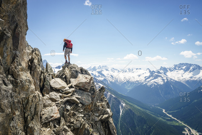 Male mountaineer standing on the edge of a cliff looking down, Canada