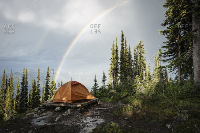 Camping tent in mountain forest with rainbow, British Columbia, Canada