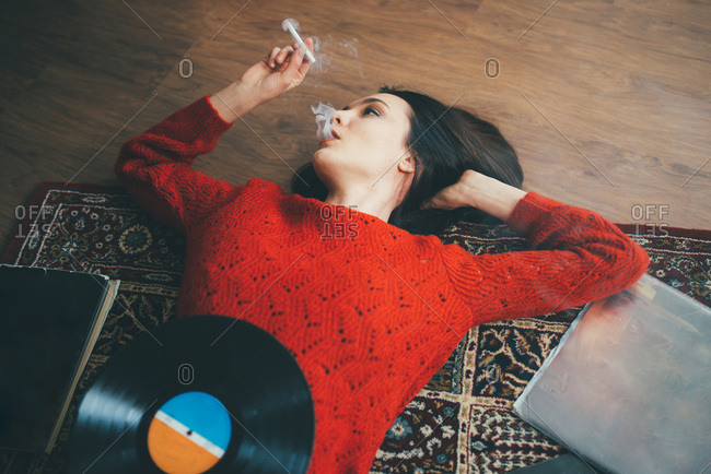 Woman lying on floor with vinyl, books and smoking cigarette.