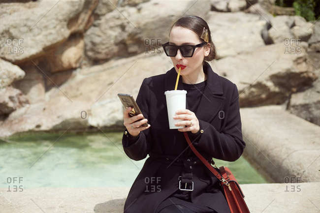 Young woman sitting by the fountain and drinking soda