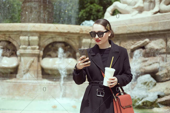 Young woman standing by the fountain and looking at her phone