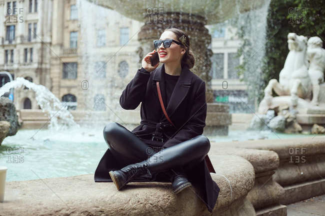 Young woman sitting by the fountain and talking on the phone