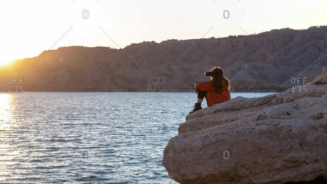 person sat down with a VR head set on looking over a lake at sunset