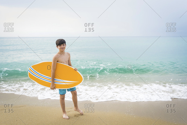 Portrait of a joyful smiling teen boy with yellow surfboard standing on the beach