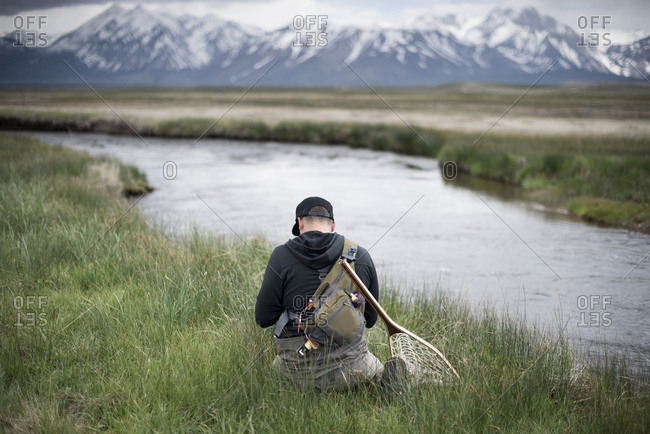 A fly fisherman prepares his gear next to a river.