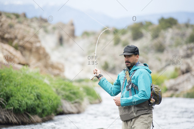 A fly fisherman casting on a beautiful river.