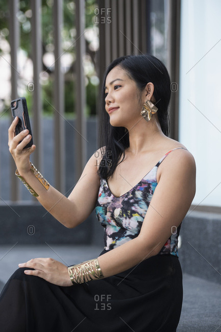Beautiful Thai woman holding her smartphone while on a video chat