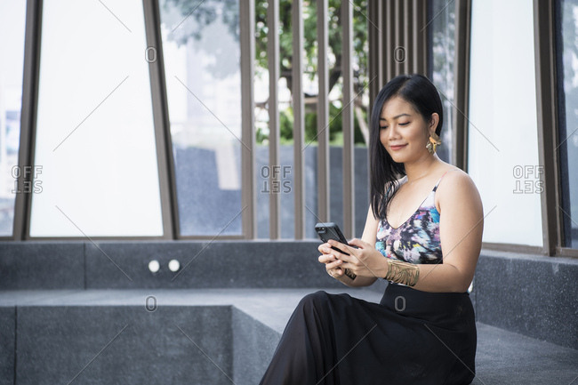 Thai woman sending text messages with her smartphone