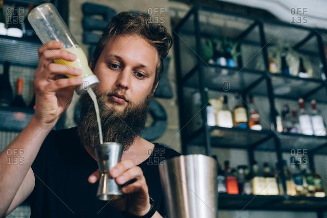 Barman With Long Beard Preparing a Mojito In A Cocktail Bar.