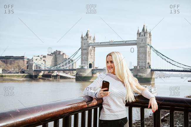 Attractive woman looking along holding mobile phone on background of Tower Bridge