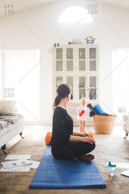 Full length of working mother exercising yoga while daughter playing in living room