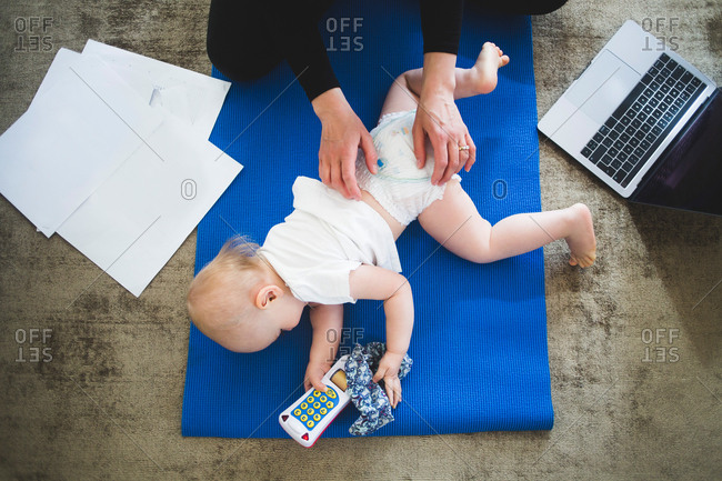 High angle view of working mother caring daughter on exercise mat at home