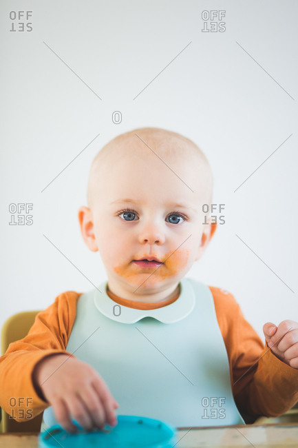 Portrait of baby girl with bib and messy mouth sitting at home