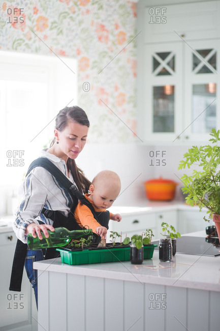 Side view of female blogger watering plants while carrying daughter in kitchen at home