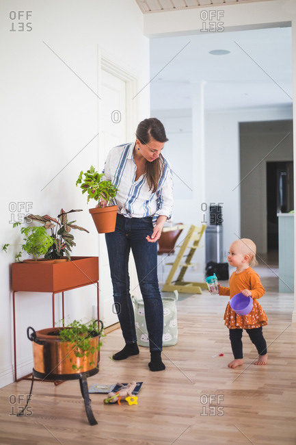 Mother holding potted plant while looking at daughter on hardwood floor in living room