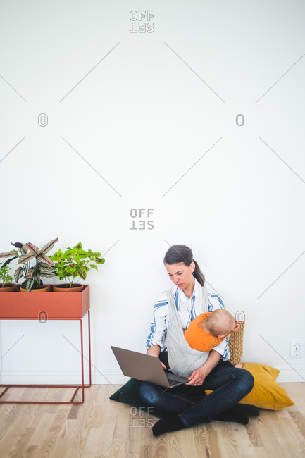 Full length of working mother using laptop while sitting with daughter against wall at home office