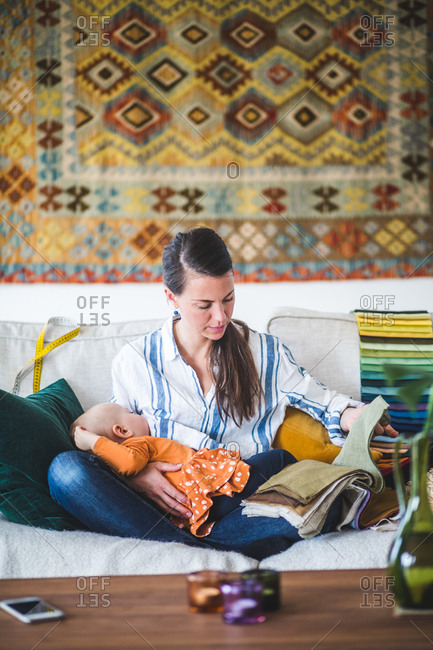 Working mother choosing fabric from swatch while breastfeeding baby girl in living room