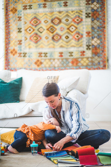 Daughter lying on busy working mother's lap in living room at home office
