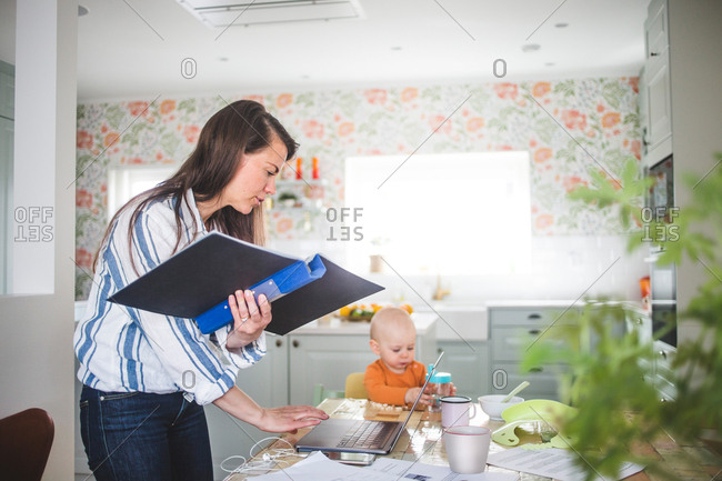 Multi-tasking mother telecommuting while daughter sitting at dining table in kitchen