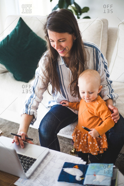 High angle view of smiling businesswoman telecommuting while sitting by daughter on sofa in living room