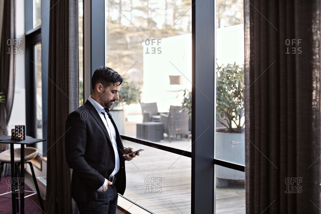 Businessman using phone while standing by window in office