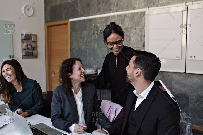 Smiling businesswoman interacting with cheerful colleagues in office