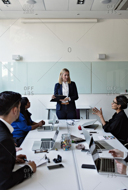 Female colleague interacting to businesswoman standing by conference table during meeting with coworkers