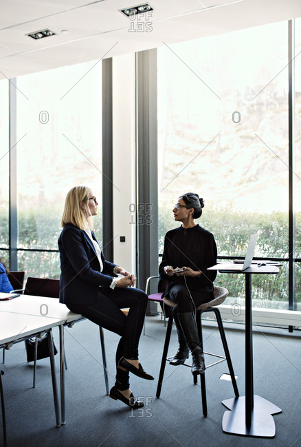 Businesswoman discussing with female colleague on chair