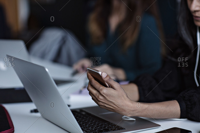 Midsection of business woman using technologies at conference table in board room