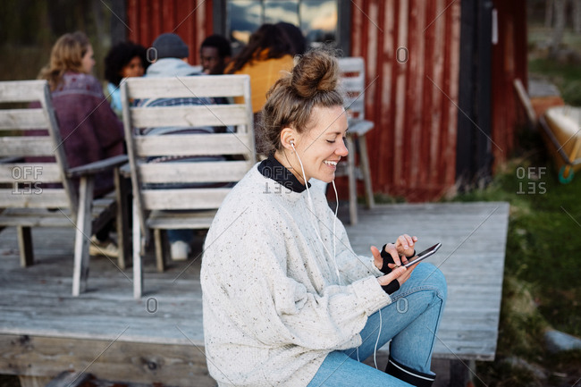 Smiling mid adult woman using smart phone while friends talking in background during sunset