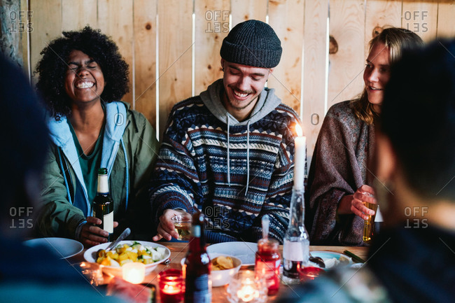 Cheerful friends holding drinks talking while sitting in log cabin