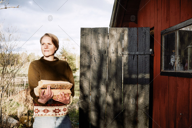 Thoughtful young woman holding firewood while standing outside cottage