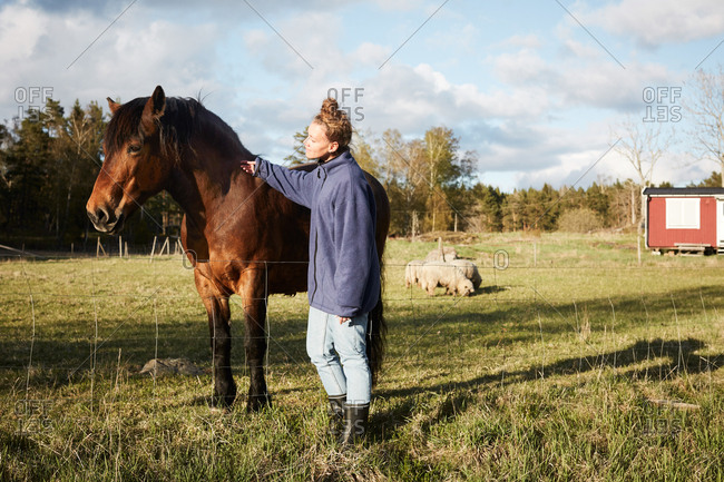Side view of mid adult woman stroking horse while standing on grassy field against sky