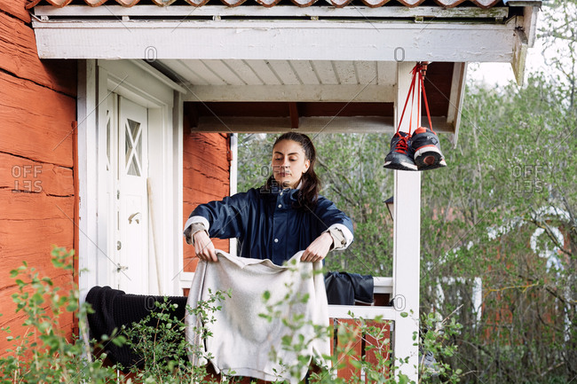 Young woman drying clothes while standing outside cottage