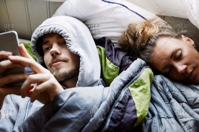 High angle view of young man using smart phone while lying by friend on bed at home