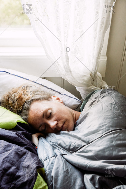 High angle view of mid adult woman sleeping on bed in cottage