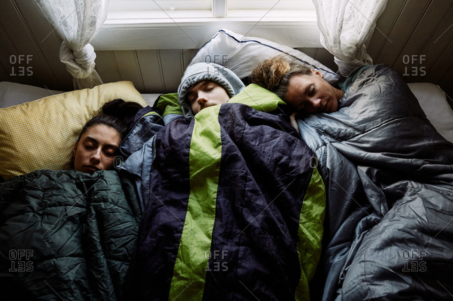 High angle view of male and female friends sleeping together on bed in cottage