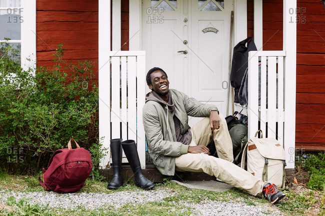Portrait of happy young man with backpacks and boots sitting outside cottage