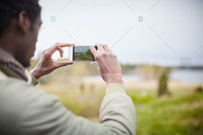 Young man photographing with mobile phone against sky