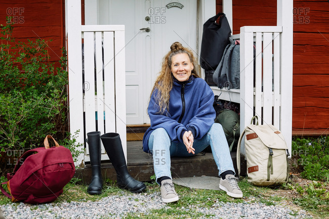 Portrait of smiling mid adult woman with backpacks and boots sitting outside cottage