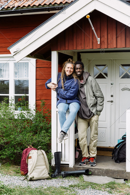 Portrait of smiling friends with backpacks at cottage entrance during weekend