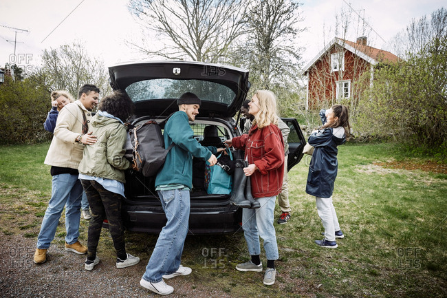 Smiling female and male friends removing luggage from car trunk on road against sky